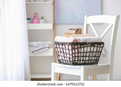 Basket with clean soft towels on chair in bathroom