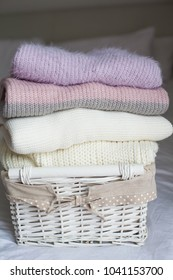 A basket with clean things on the bed. Cozy. Knitted sweaters. Fall. Spring.