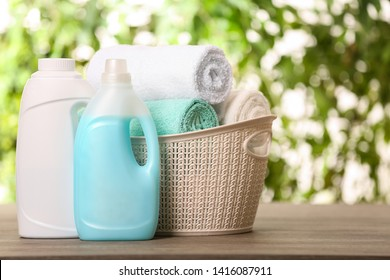 Basket with clean towels and detergents on table against blurred background. Space for text