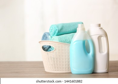 Basket with clean towels and detergents on table. Space for text