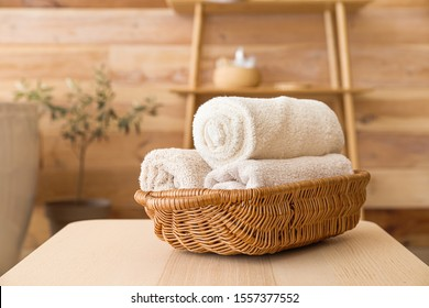 Basket with clean towels on table in bathroom