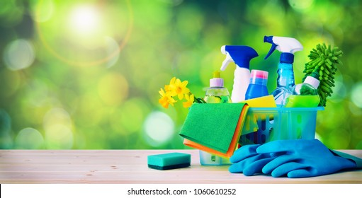 Basket with cleaning items on blurry spring background