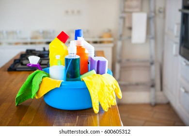 Basket with cleaning items on blurry background white citchen. Cleaning concept. Set with copy space.