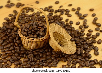 Basket with coffee beans, a handful of near spilled coffee on the table
