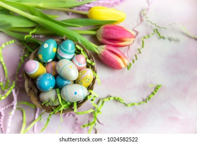 A basket of colorful Easter eggs on a light pink background with Easter grass and pink tulips.