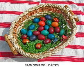 basket of colorful easter eggs on hand-woven tablecloth