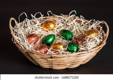 Basket of colorful easter eggs wrapped in colored foil