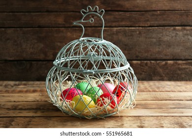 Basket with colourful Easter eggs with floral ornament on wooden background