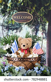"""A basket containing ateddy bear holding Israeli and American flags.  It sits in a garden among other foliage and flowers.  A sign dangles from the handle saying, """"Welcome."""""""