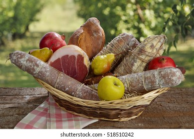 Basket of cured meats and fruits over to a board. Setting in the countryside