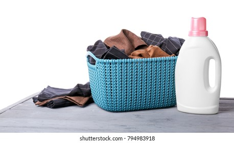 Basket with dirty clothes and laundry detergent on table against white background