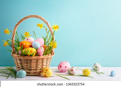 Basket of easter eggs and daffodil flower on blue background