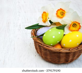 Basket with easter eggs and daffodil flowers on a old wooden background