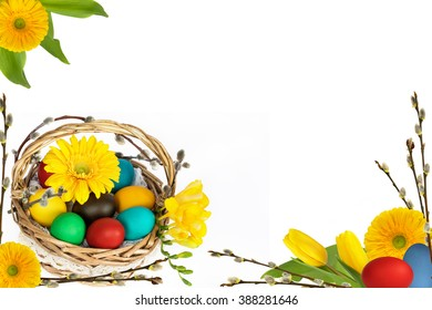 Basket with easter eggs, flowers and catkins on white background