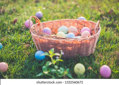 Basket with easter eggs on green grass.