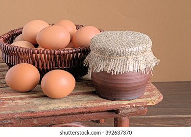 Basket with eggs and ceramic pot on old wooden table.
