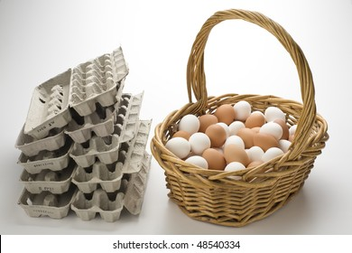Basket filled with brown and white eggs with empty  egg cartons