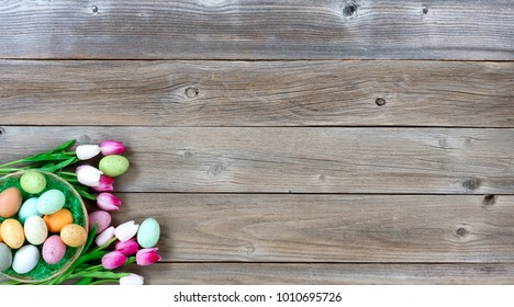 Basket filled with colorful eggs and pink tulips in lower left corner on weathered wooden boards for Easter background