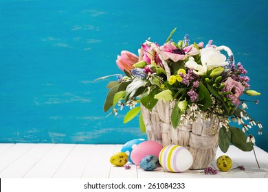Basket of flowers and easter eggs on a wooden background with space for text.
