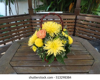 A Basket Of Flowers On The Wood Table