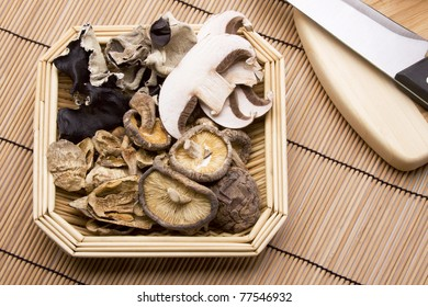 A basket of fresh and dried woodear, portobello, crimini and shitake mushrooms.