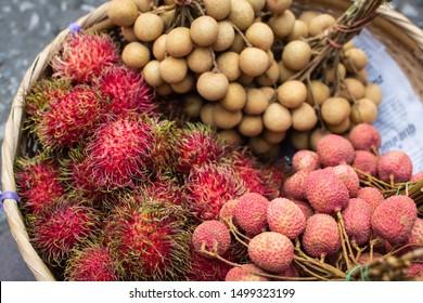 Basket with fresh exotic fruits of rambutan, lychee and longan on Asian market