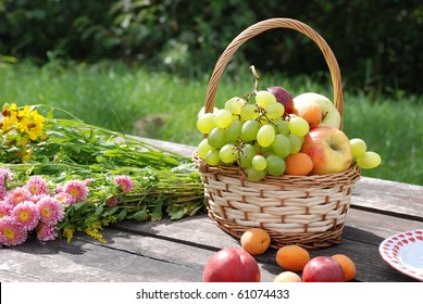 The basket with fresh fruits on the table