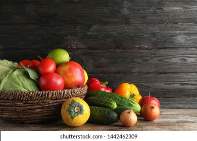 Basket with fresh fruits and vegetables on wooden table, space for text