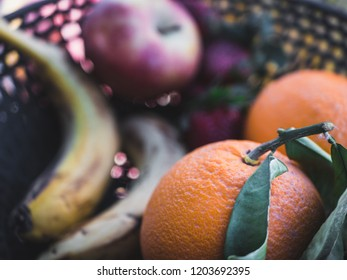 Basket with fresh Orange and Bananas and Apples in background