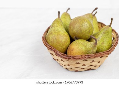 Basket with fresh pears above white background with copy space