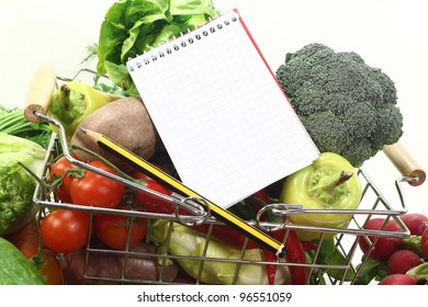 Basket with fresh vegetables, shopping list and pencil