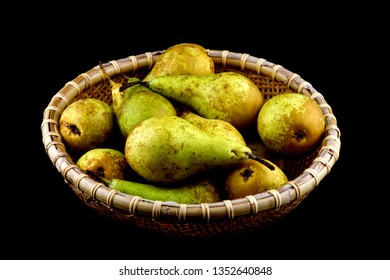 Basket of freshly picked organic pears isolated on black