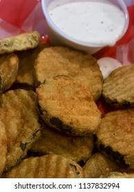 Basket of fried pickles with ranch dipping sauce.