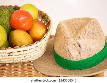 Basket of fruit and straw hat on the table. Agriculture concept