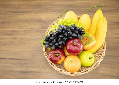 A basket of fruit. There are bananas, grapes, apples, persimmons, and oranges inside. The basket laid on brown wooden. The wooden has textures.