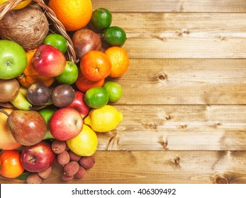 Basket of fruits on wooden background. Healthy eating and dieting concept. Winter assortment. Copy space. Top view