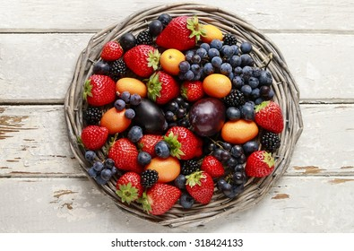 Basket of fruits: strawberries, blueberries, blackberries, grapes and kumquats.