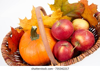 Basket full of apples and a pumpkin with some maple leaves on a white background