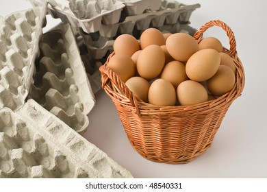 Basket full of brown eggs surronded by empty egg cartons