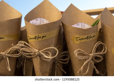 Basket full of cornets filled with rice and olive tree leaves for wedding. Selective focus