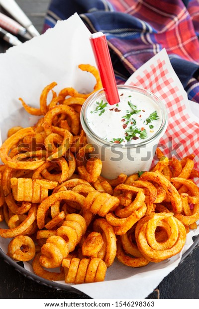 Basket full of crunchy curly fries with a jar of dip