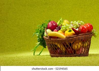 basket full of fresh produce. green background
