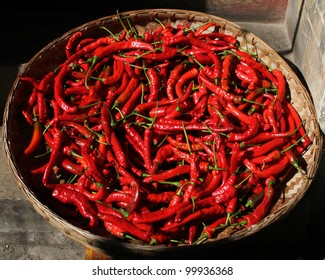 A basket full of fresh spicy chili peppers in a Chinese market.