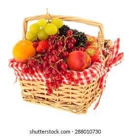 Basket full with fresh summer fruit isolated over white background