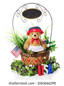 A basket full of greenery and a toy bear in patriotic attire.  A sign dangles from handle, left blank for your text..  On a white background.