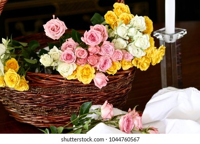 A basket full of miniature pink, white, and yellow roses a few spilling out onto a lovely off-white  tablecloth in front of a crystal candle holder with a white candle.   An elegant  still life.