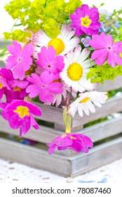 Basket full of spring garden flowers - violet and chamomile