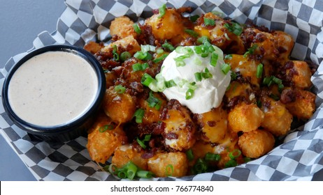 A basket of golden fried tater tots topped with co-jack cheese, bacon, sour cream and green onions. Served with a side of southwestern ranch dressing.