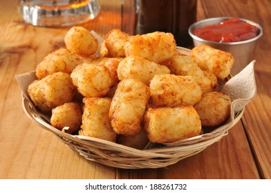 A basket of golden tater tots with beer in the background
