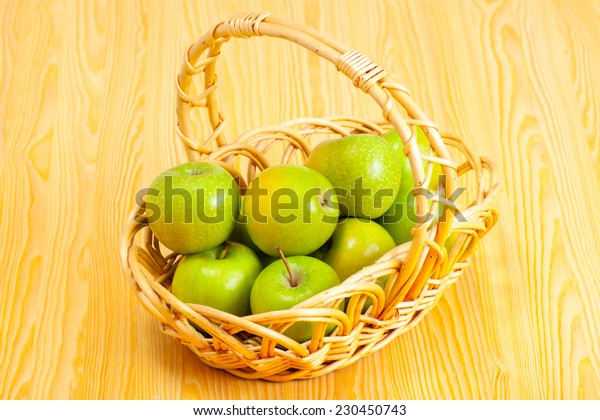 basket with green apples on a kitchen table